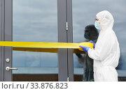 Купить «healthcare worker sealing door with caution tape», фото № 33876823, снято 24 апреля 2020 г. (c) Syda Productions / Фотобанк Лори