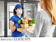 delivery girl in mask giving box of food to woman. Стоковое фото, фотограф Syda Productions / Фотобанк Лори