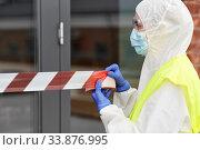 Купить «healthcare worker sealing door with caution tape», фото № 33876995, снято 24 апреля 2020 г. (c) Syda Productions / Фотобанк Лори