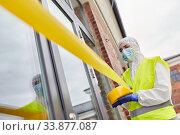 Купить «healthcare worker sealing door with caution tape», фото № 33877087, снято 24 апреля 2020 г. (c) Syda Productions / Фотобанк Лори