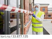Купить «healthcare worker sealing door with caution tape», фото № 33877135, снято 24 апреля 2020 г. (c) Syda Productions / Фотобанк Лори