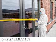 Купить «healthcare worker sealing door with caution tape», фото № 33877139, снято 24 апреля 2020 г. (c) Syda Productions / Фотобанк Лори
