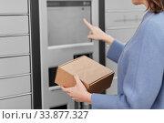 Купить «smiling woman with box at automated parcel machine», фото № 33877327, снято 22 апреля 2020 г. (c) Syda Productions / Фотобанк Лори