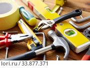 Купить «different work tools on wooden boards background», фото № 33877371, снято 26 ноября 2019 г. (c) Syda Productions / Фотобанк Лори
