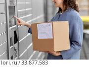 Купить «smiling woman with box at automated parcel machine», фото № 33877583, снято 22 апреля 2020 г. (c) Syda Productions / Фотобанк Лори
