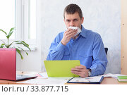 Купить «An office worker with a tablet in his hand holds a napkin at his mouth», фото № 33877715, снято 3 мая 2020 г. (c) Иванов Алексей / Фотобанк Лори