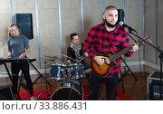Купить «Guy guitar player and singer practicing with band members in recording studio», фото № 33886431, снято 26 октября 2018 г. (c) Яков Филимонов / Фотобанк Лори