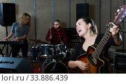 Купить «excited girl rock singer with guitar during rehearsal», фото № 33886439, снято 26 октября 2018 г. (c) Яков Филимонов / Фотобанк Лори