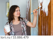 Smiling woman paints closet at home during repairs. Стоковое фото, фотограф Яков Филимонов / Фотобанк Лори