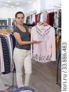 Woman demonstrating blouse on hanger. Стоковое фото, фотограф Яков Филимонов / Фотобанк Лори