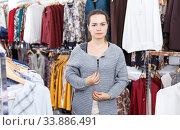 Woman trying new jacket in clothing store. Стоковое фото, фотограф Яков Филимонов / Фотобанк Лори