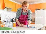 Elderly woman housewife in apron cleaning furniture at kitchen. Стоковое фото, фотограф Яков Филимонов / Фотобанк Лори