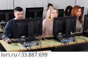 Купить «Young and older businesswomen and businessmen in open plan office», фото № 33887699, снято 20 февраля 2019 г. (c) Яков Филимонов / Фотобанк Лори