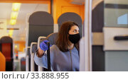 Купить «woman in protective face mask in electric train», видеоролик № 33888955, снято 25 мая 2020 г. (c) Syda Productions / Фотобанк Лори