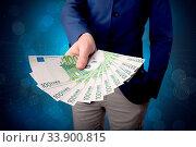 Купить «Young businessman holding large amount of bills with shiny blue background», фото № 33900815, снято 11 июля 2020 г. (c) easy Fotostock / Фотобанк Лори