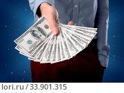 Купить «Young businessman holding large amount of bills with light beams behind him», фото № 33901315, снято 11 июля 2020 г. (c) easy Fotostock / Фотобанк Лори