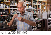 Mature man inspecting quality of red wine. Стоковое фото, фотограф Яков Филимонов / Фотобанк Лори
