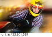 Купить «Man in helmet and other people driving car for karting», фото № 33901599, снято 18 марта 2019 г. (c) Яков Филимонов / Фотобанк Лори