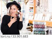 Woman customer in hat trying earrings. Стоковое фото, фотограф Яков Филимонов / Фотобанк Лори