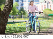 Smiling happy Caucasian teen age girl riding modern bicycle on a city park, looking at camera. Стоковое фото, фотограф Кекяляйнен Андрей / Фотобанк Лори