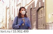 Купить «woman in medical mask with tumbler walking in city», видеоролик № 33902499, снято 28 мая 2020 г. (c) Syda Productions / Фотобанк Лори