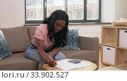 Купить «african woman with papers and calculator at home», видеоролик № 33902527, снято 24 мая 2020 г. (c) Syda Productions / Фотобанк Лори