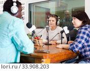 Купить «Multinational group of cheerful young adults emotionally discussing in radio studio», фото № 33908203, снято 16 марта 2019 г. (c) Яков Филимонов / Фотобанк Лори