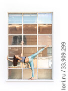 Купить «Fit sporty active girl in fashion sportswear doing yoga fitness exercise in front of gray wall, outdoor sports, urban style», фото № 33909299, снято 24 мая 2019 г. (c) Matej Kastelic / Фотобанк Лори