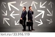 Купить «Young conflicted businessman choosing between two directions with arrows around him», фото № 33916119, снято 8 июля 2020 г. (c) easy Fotostock / Фотобанк Лори