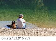 Купить «Badender Schäferhund mit Frau am Seeufer. Frau genießt die Sonne, der Hund das kühlende Nass.», фото № 33916739, снято 5 июня 2020 г. (c) age Fotostock / Фотобанк Лори