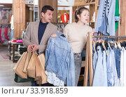 Купить «Smiling woman and man are choosing clothes and looking on jeans blouse», фото № 33918859, снято 12 марта 2018 г. (c) Яков Филимонов / Фотобанк Лори