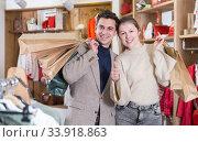 Купить «Young woman and man are standing satisfied with packadge after shopping», фото № 33918863, снято 12 марта 2018 г. (c) Яков Филимонов / Фотобанк Лори