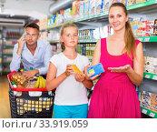 Cheerful woman and teenager girl in the grocery shop. male on backdrop. Стоковое фото, фотограф Яков Филимонов / Фотобанк Лори