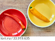 Yellow pod of sweet pepper on a yellow plate near to red pod on a red plate on a wooden tabletop. Стоковое фото, фотограф Евгений Харитонов / Фотобанк Лори