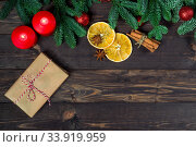 Купить «Gift wrapped in rough paper and hand-made jewelry on a wooden table surrounded by fir branches, space for inscription in the center», фото № 33919959, снято 30 декабря 2018 г. (c) Константин Лабунский / Фотобанк Лори