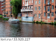 Leeds, west yorkshire, united kingdom: 16 july 2019: a boat sailing past calls laning in the river aire in leeds west yorkshire. Стоковое фото, фотограф Zoonar.com/PHILIP_OPENSHAW / age Fotostock / Фотобанк Лори