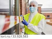 Купить «healthcare worker sealing door with caution tape», фото № 33928583, снято 24 апреля 2020 г. (c) Syda Productions / Фотобанк Лори