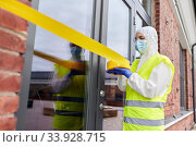 Купить «healthcare worker sealing door with caution tape», фото № 33928715, снято 24 апреля 2020 г. (c) Syda Productions / Фотобанк Лори