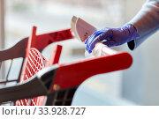 Купить «hand cleaning shopping cart handle with wet wipe», фото № 33928727, снято 30 апреля 2020 г. (c) Syda Productions / Фотобанк Лори