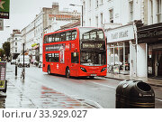 London, United Kingdom - August 18, 2017: The streets of London during the rain. Red phone boxes and red london buses. Редакционное фото, фотограф Nataliia Zhekova / Фотобанк Лори