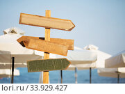 Wooden pointer post with copy space at the beach. arrows on a guidepost pointing at the sea. Signpost showing the way to the beach resorts. Стоковое фото, фотограф Nataliia Zhekova / Фотобанк Лори