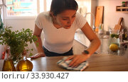 Купить «Mexican woman housewife is cleaning furniture at home kitchen», видеоролик № 33930427, снято 26 мая 2020 г. (c) Яков Филимонов / Фотобанк Лори