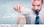 Купить «Young handsome businessman using wooden building blocks with data and calculations behind him», фото № 33935727, снято 7 августа 2020 г. (c) easy Fotostock / Фотобанк Лори