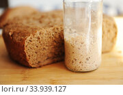 Freshly baked homemade rye-wheat whole grain bread and rye sourdough in a glass jar. Close up. Стоковое фото, фотограф Кристина Сорокина / Фотобанк Лори