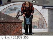 Пожилая женщина ищет чтото в своей сумке у входа на станцию метро Тверская на Тверской площади в центре города Москвы, Россия (2020 год). Редакционное фото, фотограф Николай Винокуров / Фотобанк Лори
