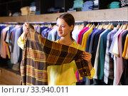 Купить «Satisfied woman chooses fashionable checkered shirt», фото № 33940011, снято 12 июля 2020 г. (c) Яков Филимонов / Фотобанк Лори