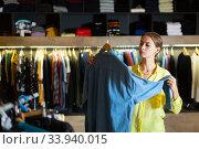 Young woman chooses denim shirt. Стоковое фото, фотограф Яков Филимонов / Фотобанк Лори