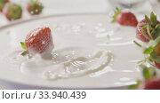 Купить «Close-up drops of milk and ripe red strawberry fruit falls into a plate with milk splashes. A few berries lie on the white plate. Slow motion. Soft focus. Full HD video, 240fps,1080p.», видеоролик № 33940439, снято 2 июля 2020 г. (c) Ярослав Данильченко / Фотобанк Лори