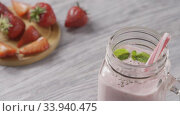 Купить «Panoramic slow motion video to a jar with strawberry milk smoothies with chia seeds, a leaf of mint and plastic straws in it. Background of strawberry fruit on a wooden board. Full HD, 240fps,1080p.», видеоролик № 33940475, снято 6 июля 2020 г. (c) Ярослав Данильченко / Фотобанк Лори