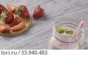 Panoramic slow motion video of jar with strawberry milk smoothies with chia seeds, a leaf of mint and plastic straws in it. Background of strawberry fruit on a wooden board. Full HD, 240fps,1080p. Стоковое видео, видеограф Ярослав Данильченко / Фотобанк Лори